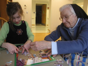Sister Virginia helps a young friend with a puzzle.