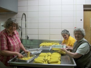 Ss. Corrine Lemmer, Theresa Lafferty and Patricia Heirigs cleaning corn.